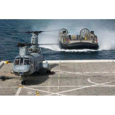 A hovercraft approaches USS New Orleans as a CH-46E Sea Knight sits on the flight deck Canvas Art - Stocktrek Images (35 x 23)
