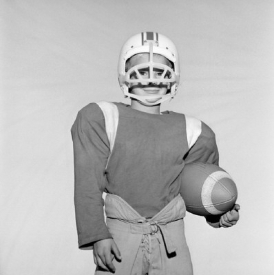 Boy wearing football helmet and holding football Poster Print