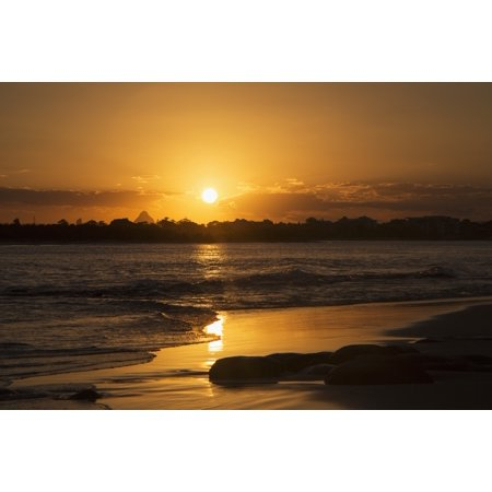 A golden sun sets over silhouetted trees and reflects on the wet beach along the coast Caloundra Queensland Australia Stretched Canvas - John Short  Design Pics (19 x (Gold Set Pics)