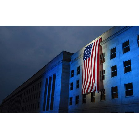 - A memorial flag is illuminated on The Pentagon Poster Print by Stocktrek Images