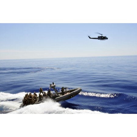 A US Navy UH-1N Huey helicopter provides cover for US Marines on a rigid hull inflatable boat Print