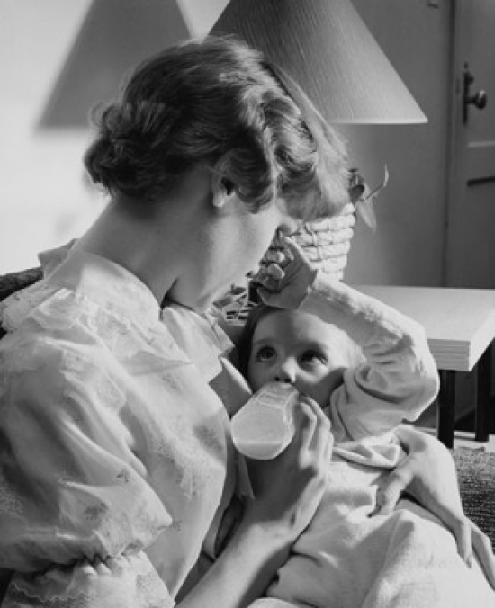 Young woman feeding her baby with a baby bottle Poster Print by Posterazzi
