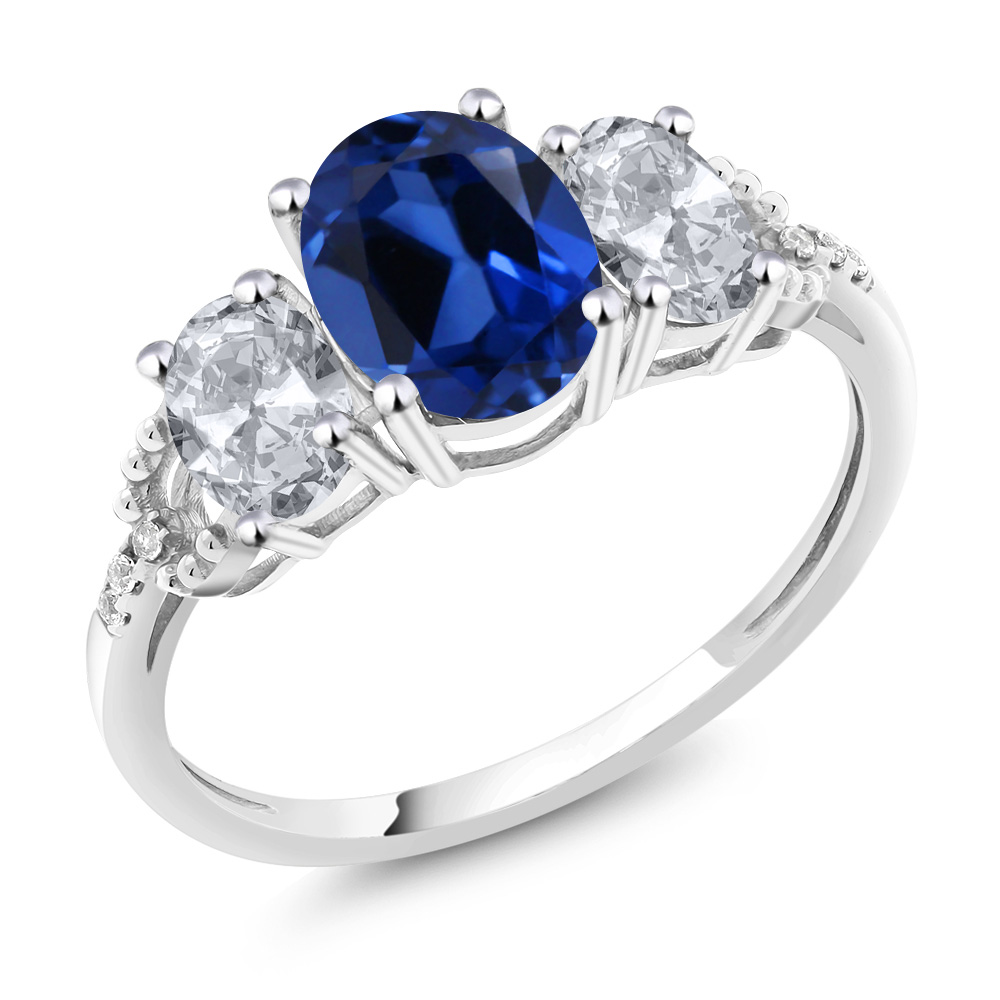 10K White Gold Diamond Accent Three-Stone Engagement Ring set with 2.65 Ct Oval Blue Simulated Sapphire White Topaz by