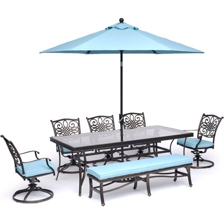"Image of ""Hanover Traditions 7-Piece Dining Set in Blue with 5 Swivel Rockers, Bench, 42""""x84"""" Glass-Top Table, and 11 Ft. Umbrella with Stand"""