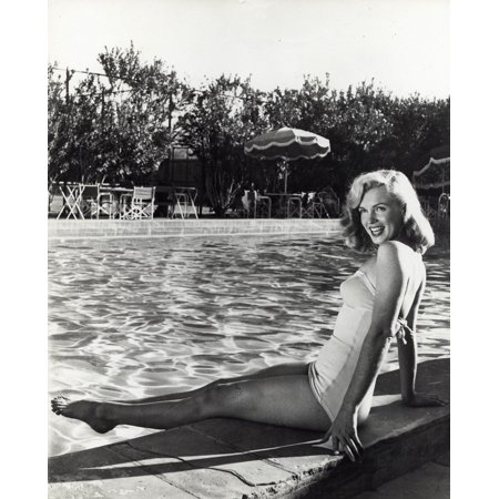 Marilyn Monroe sitting next to a swimming pool Photo