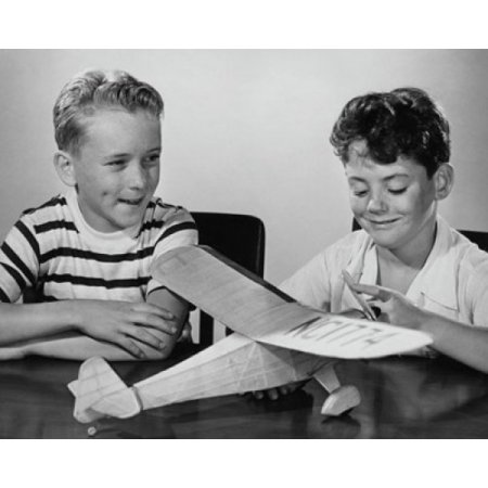 Boy making a model airplane and another boy sitting beside him Stretched  Canvas - (24 x 36)