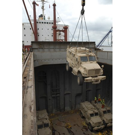 A harbor crane lifts a mine-resistant ambush-protected vehicle from the hull of a cargo vessel Poster - Harbor Crane
