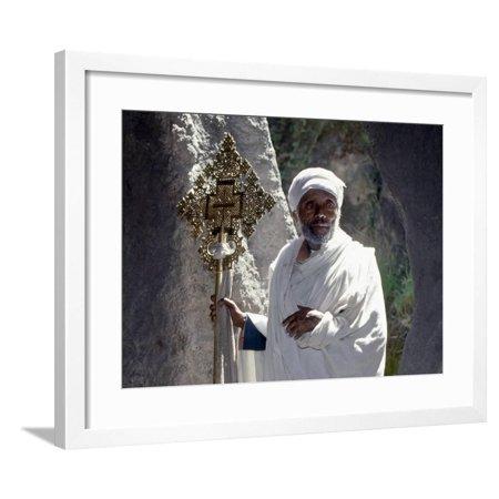 Old Ethiopian Orthodox Priest Holds a Large Brass Coptic Cross at Rock-Hewn Church of Adadi Maryam Framed Print Wall Art By Nigel Pavitt