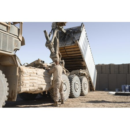 A motor vehicle operator with Combat Logistics Battalion offloads a shipping container of supplies from a Logistical Vehicle System Replacement at Forward Operating Base Pennsylvania Afghanistan Poste