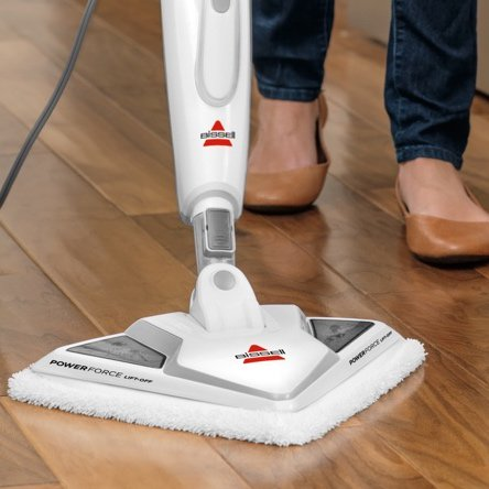 A stick sweeper cleaning hardwood floors. Links to a blog post about floorcare that's best for hardwood floors including sweepers and vacuums for hard floors.