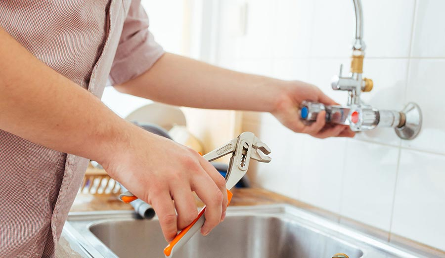woman's hands fixing leaky faucet