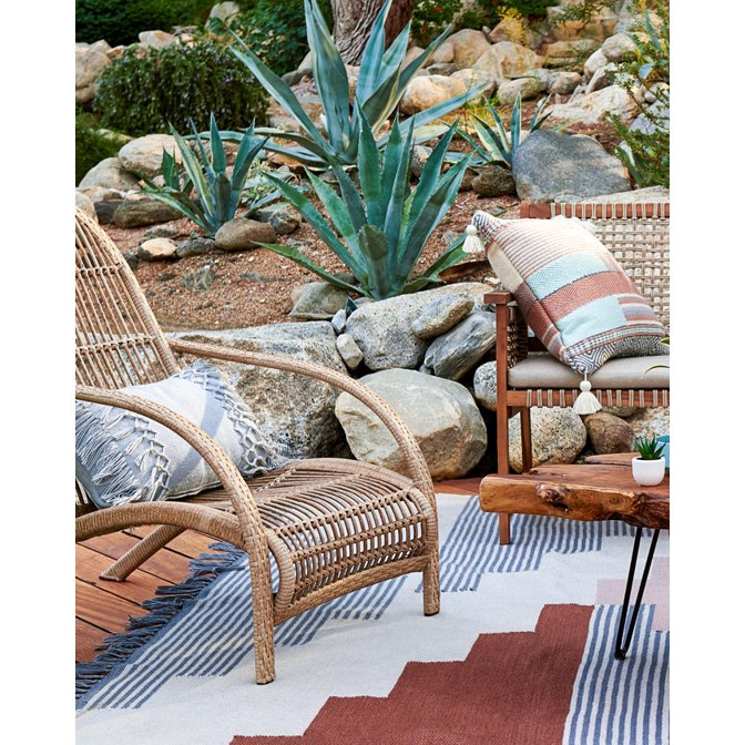 A natural bohemian outdoor living setting with woven chairs and colorful outdoor pillows.