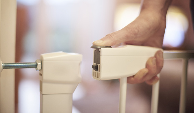 Baby gate buying guide - close up of a hand closing the lock of a pressure-mounted baby gate
