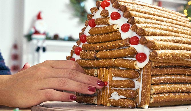 Adding pretzel door to gingerbread log cabin made of pretzels