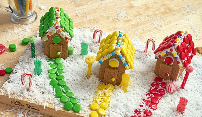 3 colorful candy cottages made out of graham crackers