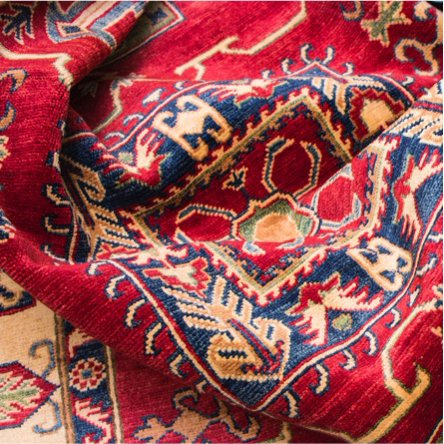 Colorful area rugs folded on top of each other. Links to a blog post about how to clean area rugs.