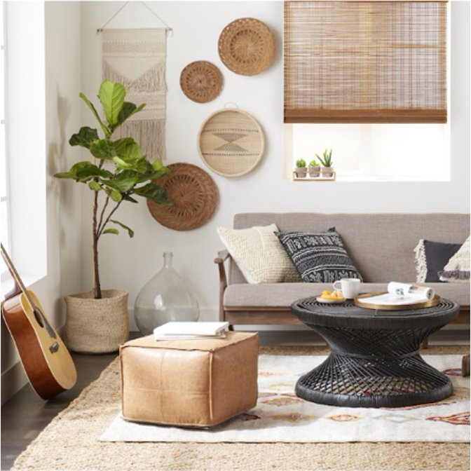 A natural bohemian living room with a leather pouf, modern loveseat, and woven round coffee table.