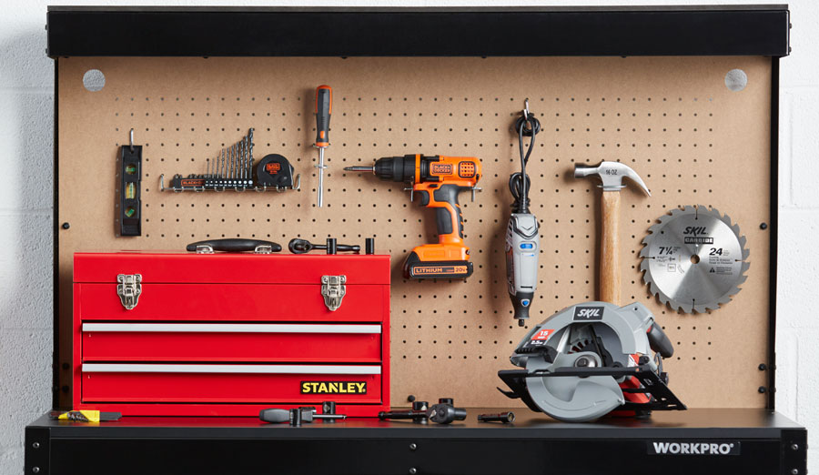 Work bench with corkboard featuring drills, tool box and other home improvement equipment