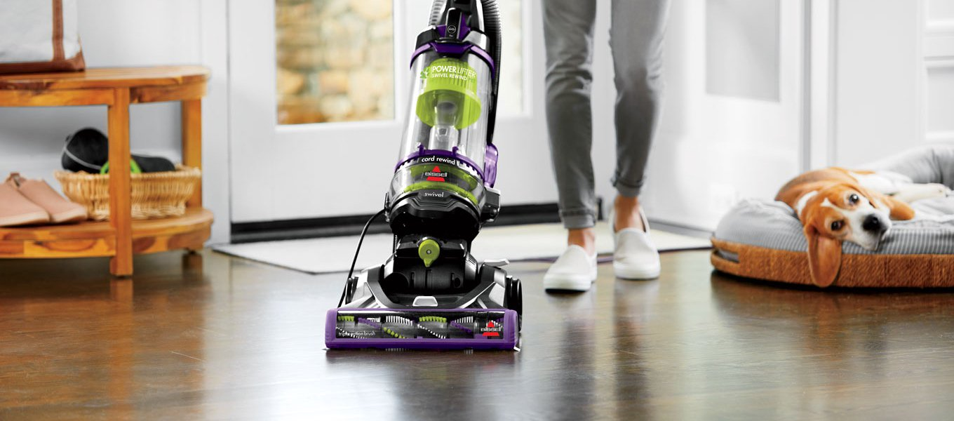 A person vacuuming with a bagless upright vacuum next to a dog in a pet bed. Links to a blog post about how to find the best vacuum for your home.