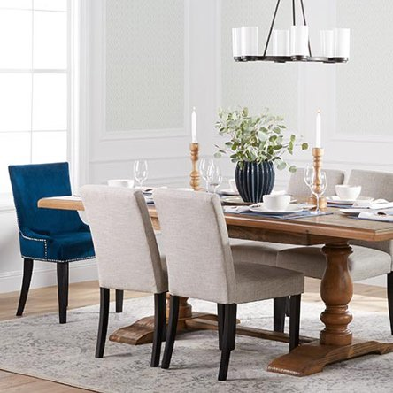 A transitional style dining room with blue velvet end chairs, a wooden traditional trestle table, and a traditional style chandelier.
