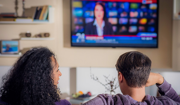 Two people watching LED TV