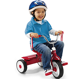Young boy wearing a helmet riding a red kids' tricycle