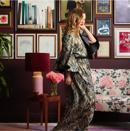 Drew Barrymore in a long paisley print gown in front of a sophisticated gallery wall. Links to a blog post introducing Drew Barrymore Flower Home.