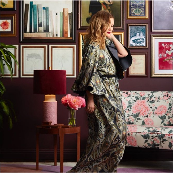 Drew Barrymore in a dark green robe standing in front of a moody modern gallery wall by Drew Barrymore Flower Home and a floral settee.