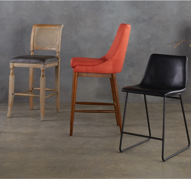 Three bar stools in different styles against a trendy concrete background as the intro to our barstool buying guide.