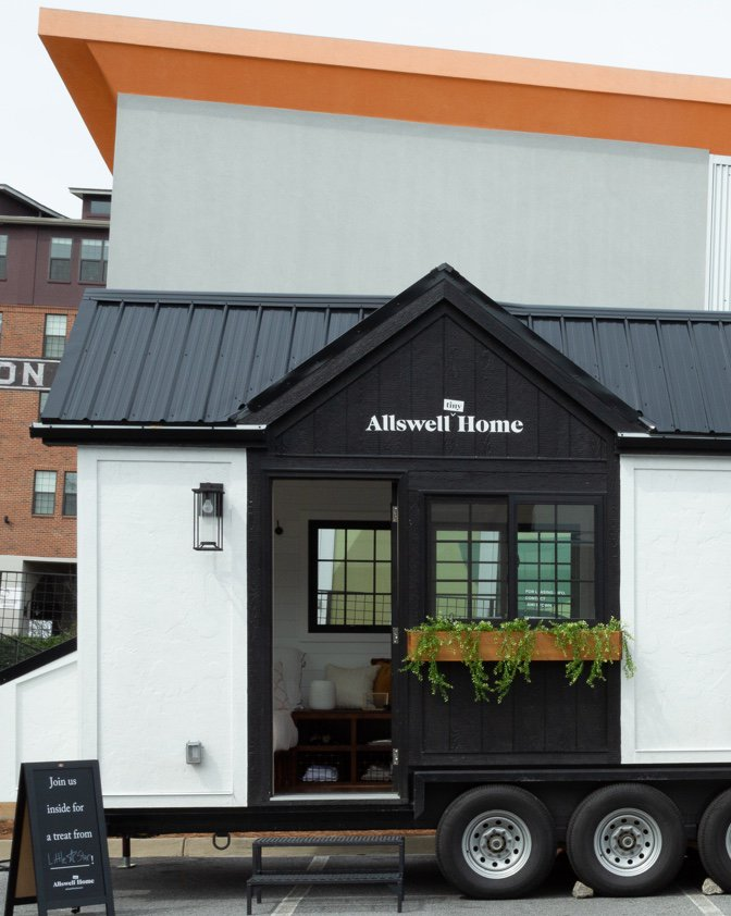 The exterior of the Allswell Tiny Home with its pitched roof and little garden planters.