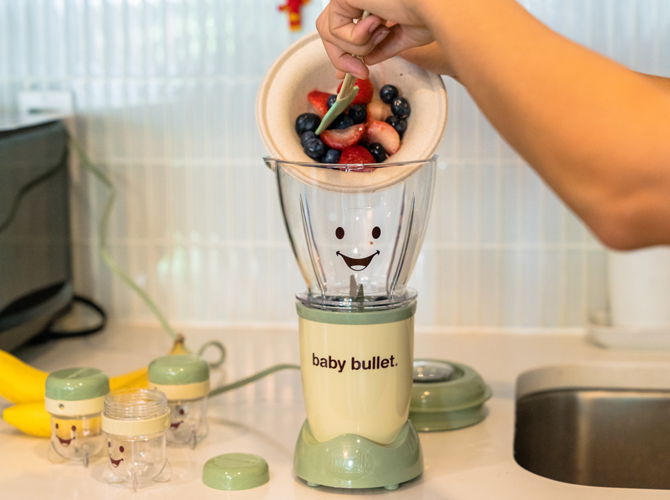 Mom's hand spooning strawberries and blueberries into a Baby Bullet food blender to make food for her baby