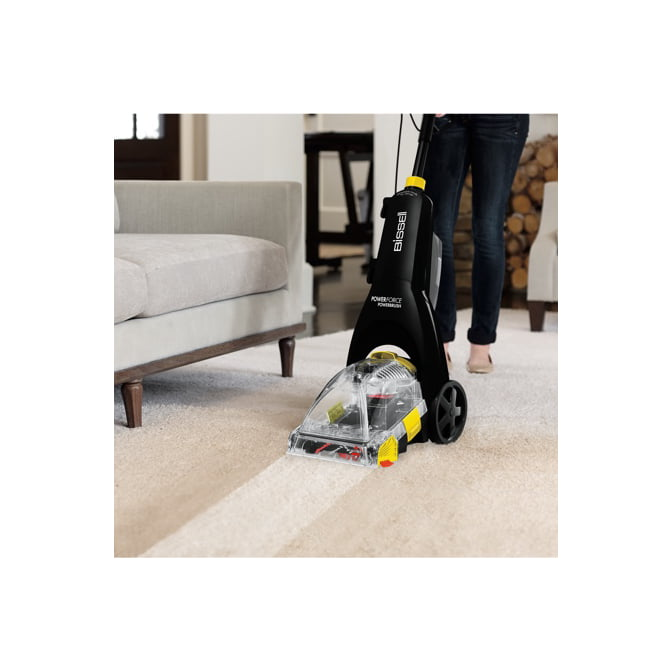 Someone using a carpet cleaner to clean dirt out of carpets in a living room with