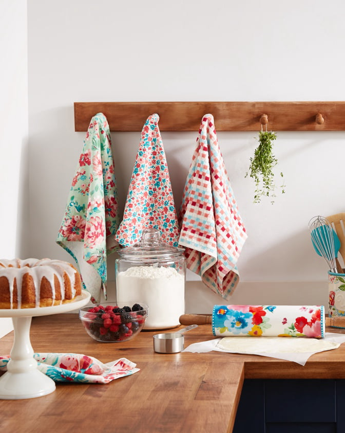 A set of kitchen towels from The Pioneer Woman hanging on wooden wall hooks above a wooden kitchen counter with baking supplies. Links to where to shop for the best kitchen towels.
