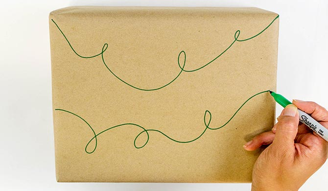 Drawing in green pen on kraft paper for pom pom light garland how to
