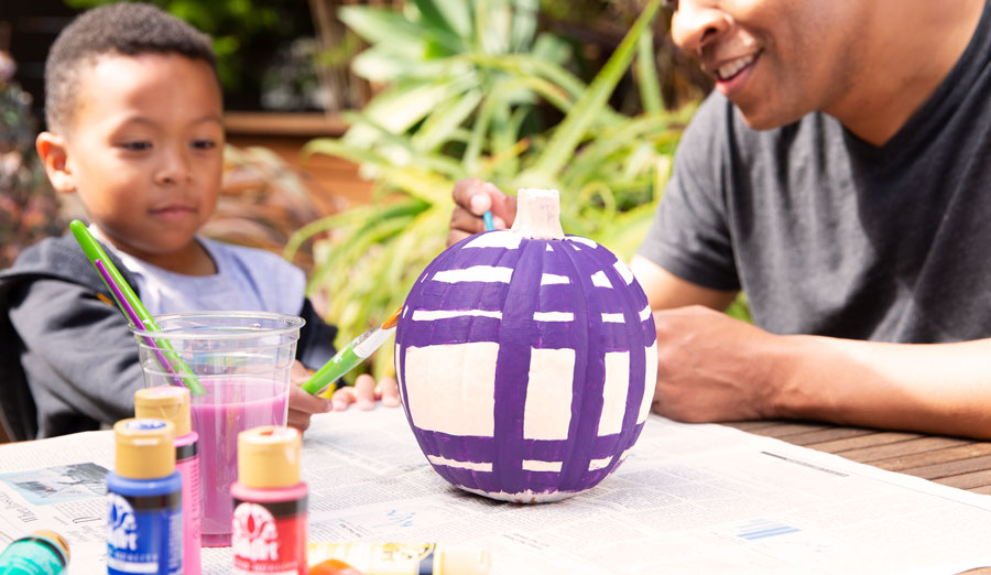 Father and son painting purple stripes on a white pumpkin