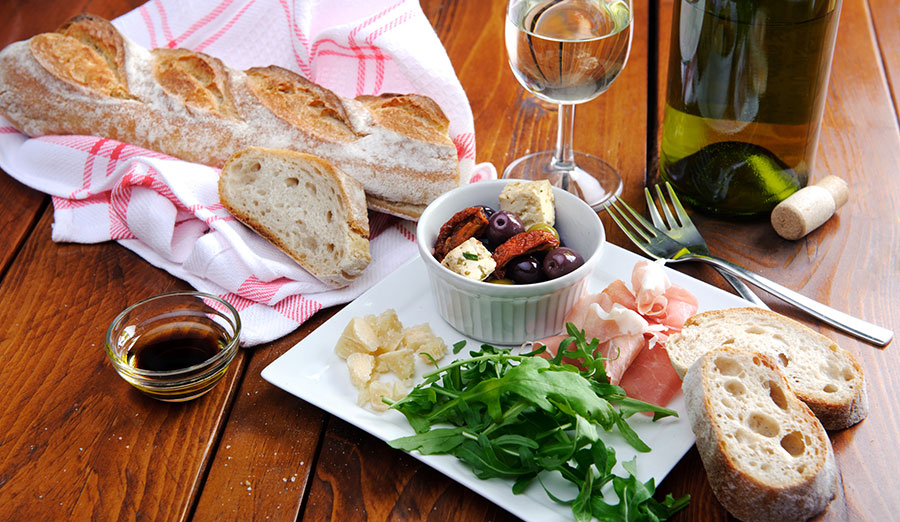 spread of bread, cheese and vegetables with a glass of white wine