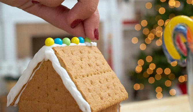 Decorating roof with candy for graham cracker candy house