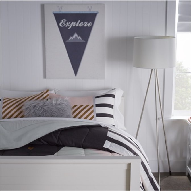 Black and white twin bed in a first apartment with pennant flag decor.