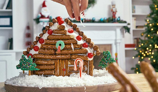 Adding coconut snow to completed gingerbread house log cabin