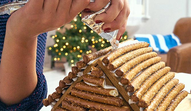 Adding roof snow to gingerbread log cabin made with pretzels