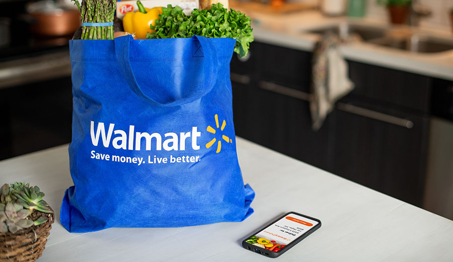 Groceries in Walmart bag next to phone