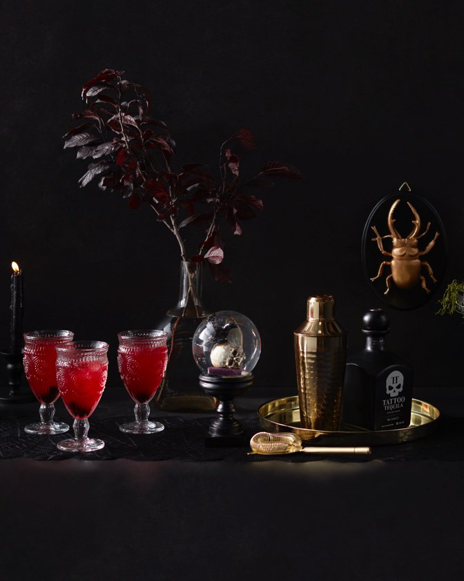 Beautiful and bewitching Halloween decor with golden beetles, glass goblets, and more.