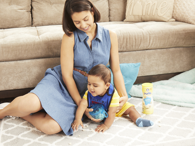 Mom sitting on the floor with baby boy wearing a blue bib and yellow romper, baby is eating baby finger food out of a bowl