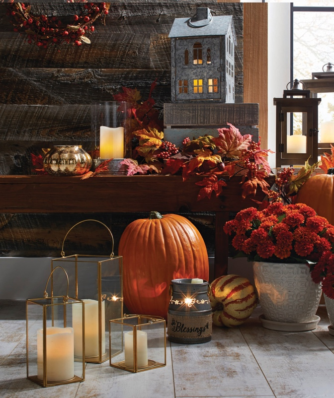 An entryway bench decorated with a galvanized metal lantern shaped like a house, lots of fall foliage, a pumpkin and candles.