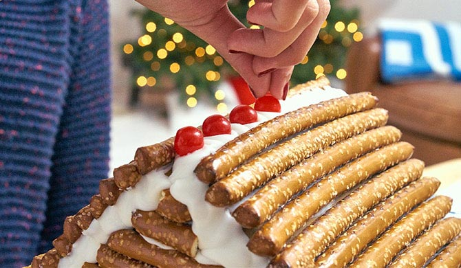 Decorating gingerbread log cabin roof with red candies