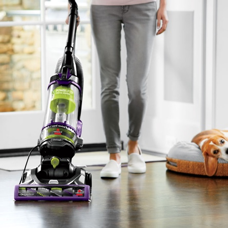 A woman vacuuming with an upright pet vacuum on hardwood floors next to her dog in a dog bed.