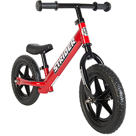 Red toddlers' Strider balance bike with black wheels