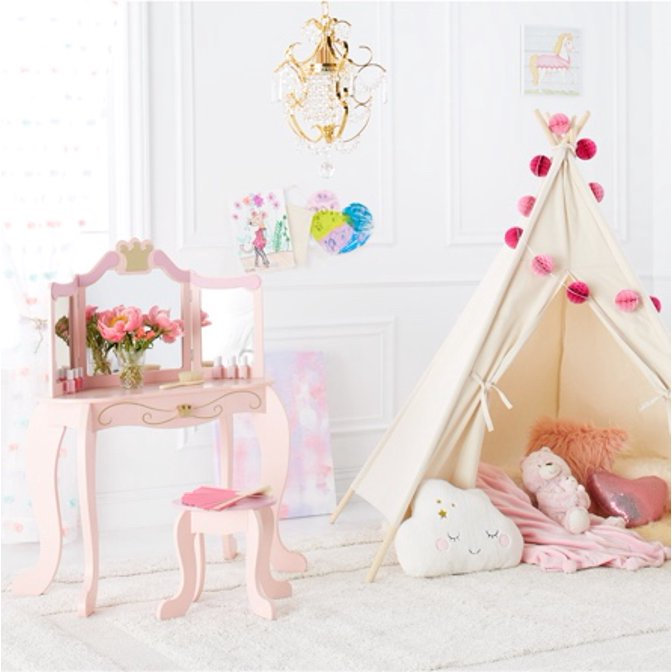 A girls room with a pink vanity, a tee pee with decorative pom poms and fun wall art