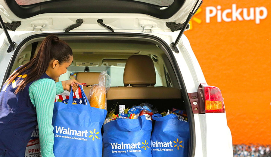 Walmart associate putting bags into car at Grocery Pickup