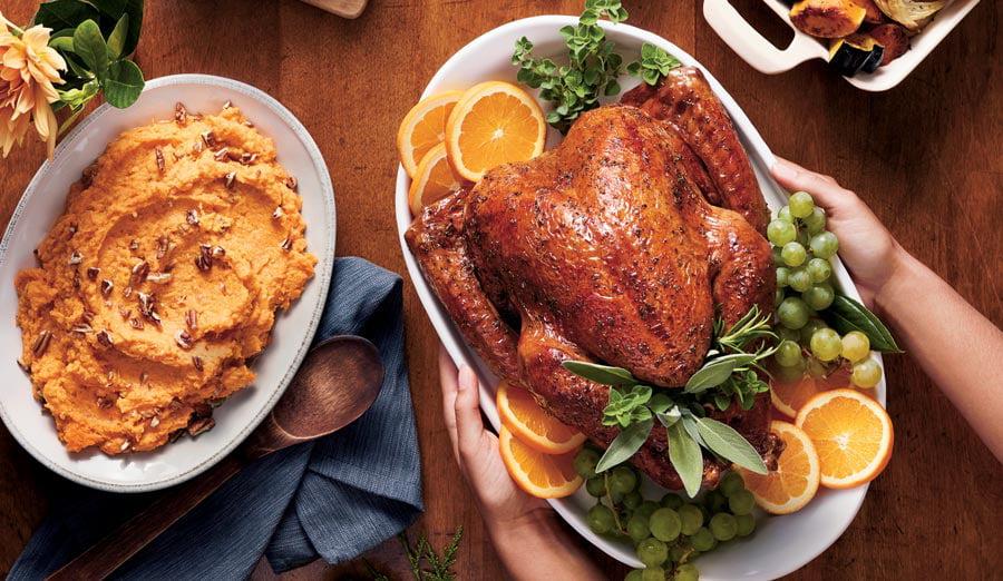 Hands holding Thanksgiving turkey on platter